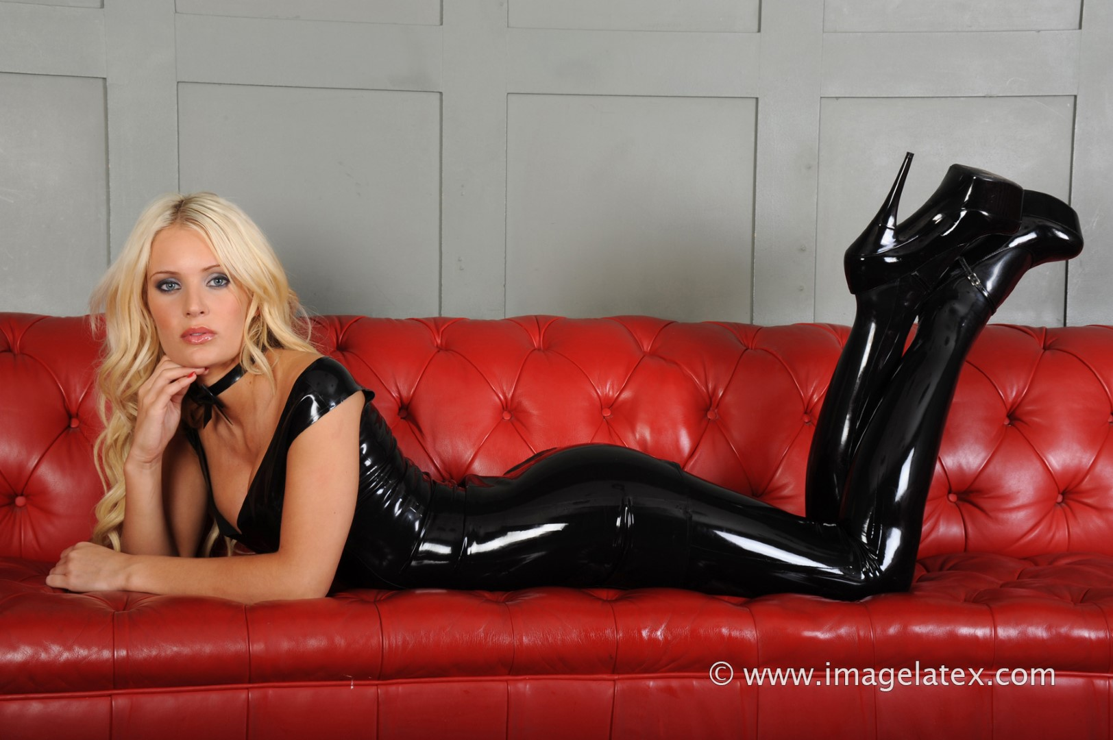 beautiful blonde alessandra poses on a couch in skin tight shiny